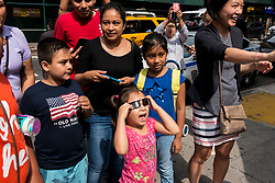 August 21, 2017 - A little girl screams with delight as her family stops on the sidewalk to allow her to look at the solar eclipse through solar filtered glasses in New York city.
