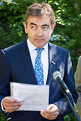 "© Licensed to London News Pictures. 19/05/2014. London, England. Pictured: Actor Rowan Atkinson reading war poems. Show Garden ""No Man's Land: ABF The Soldiers' Charity Garden to mark the centenary of World War One.  Press Day at the RHS Chelsea Flower Show. On Tuesday, 20 May 2014 the flower show will open its doors to the public.  Photo credit: Bettina Strenske/LNP"