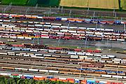 Nederland, Zuid-Holland, Zwijndrecht, 15-07-2012; Kijfhoek, rangeerterrein voor goederentreinen. Details opstelling treinen. .Kijfhoek huisvest Keyrail, exploitant Betuweroute en is in beheer bij ProRail. De Betuweroute, die begint als Havenspoorlijn op de Maasvlakte, verbindt via Kijfhoek de Rotterdamse haven met het achterland. Het rangeeremplacement dient voor het sorteren van goederenwagons waarbij gebruik gemaakt wordt van de zwaartekracht, het 'heuvelen': de wagons worden de heuvel opgeduwd, bij het de heuvel afrollen komen ze, door middel van wissels, op verschillende verdeelsporen. Railremmen zorgen voor het automatisch remmen van de wagons. Na het heuvelproces staan de nieuw samengestelde treinen op aparte opstelsporen..Kijfhoek, railway yard used by ProRail and Keyrail (Betuweroute operator). Kijfhoek connects via the Betuweroute (beginning as Havenspoorlijn on the Maasvlakte), through the port of Rotterdam with the hinterland. The shunting yard for sorting wagons makes use of gravity. The new trains are assembled on separate tracks..luchtfoto (toeslag), aerial photo (additional fee required).foto/photo Siebe Swart