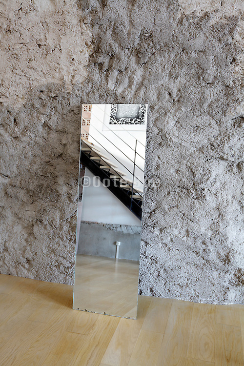 a mirror casually placed against a rough cemented wall