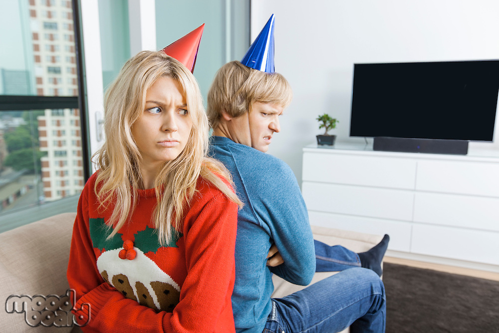 Annoyed couple in Christmas sweaters and party hats sitting back to back at home