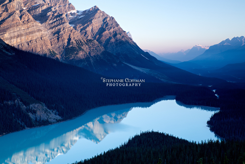 Calm blue water fills this glacially fed lake shaped like a wolf's head in Banff National Park, Alberta