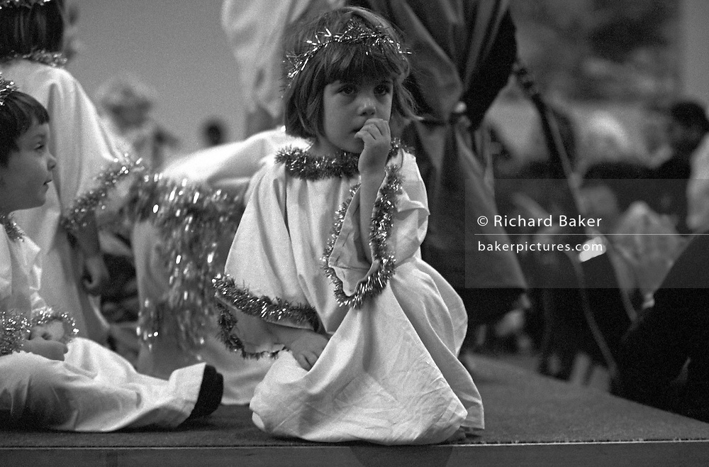 A four year-old looks unhappy and a little nervous during their playgroup's Christmas nativity play in a local church.