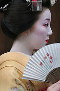 MAIKO GIRL, APPRENTICE GEISHA, KYOTO, JAPAN. Wearing traditional red lipstick, white make-up, with fan and kimono. The Gion Geisha district is featured in the 'Memoirs of a Geisha' book, by Arthur Golden, made into a movie by Steven Spielberg.