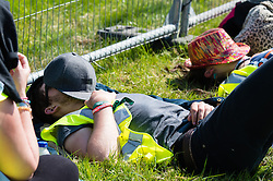 © Licensed to London News Pictures. 11/06/2015. Newport, UK.  Staff at Isle of Wight Festival 2015 sleep  with hats over their faces in the hot sun on day 1 of the festival, during a rest break. Today has been hot and sunny.  This years festival include headline artists the Prodigy, Blur and Fleetwood Mac.  Photo credit : Richard Isaac/LNP
