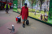 Elderly woman woman struggles with shopping past a regeneration project hoarding image at Elephant & Castle, London borough of Southwark.