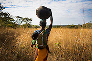 Jacinta Zelinto's daughter Elverina on her way to go and collect water, Namissimbe, Mozambique