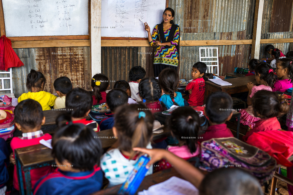 A primary school teacher tries to conduct a class in the temporary shed in which the Jyugal school is running in Chautara, Sindhupalchowk, Nepal on 29 June 2015. Although school has resumed in temporary sheds, classes are unable to return to normal because there are no walls between classrooms. Photo by Suzanne Lee for SOS Children's Villages