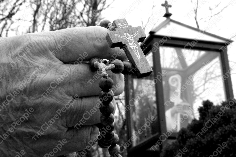 A pilgrim stops and prays with her beads as a sign of devotion to St. Bridget at the well in Liscannor during the week.<br />