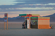 """Drinking from the gas pump at Awful's Gas & Snack<br /> by: Matthew Gerring & Crank Factory<br /> from: San Francisco, CA<br /> year: 2019<br /> <br /> Awful's Gas & Snack: Your Gateway to the Big Wild! See one of the few remaining gasoline stations, painstakingly preserved since the mid-21st century. Travel back to a time when hardy men roamed the """"open road"""" seeking fortune & freedom. Wilderness passes & provisions available. NO GAS AVAILABLE FOR PURCHASE, PLEASE DON'T ASK.<br /> <br /> URL: http://awfulsgas.com<br /> Contact: awfuls@awfulsgas.com<br /> <br /> https://burningman.org/event/brc/2019-art-installations/?yyyy=&artType=H#a2I0V000001AVwVUAW"""