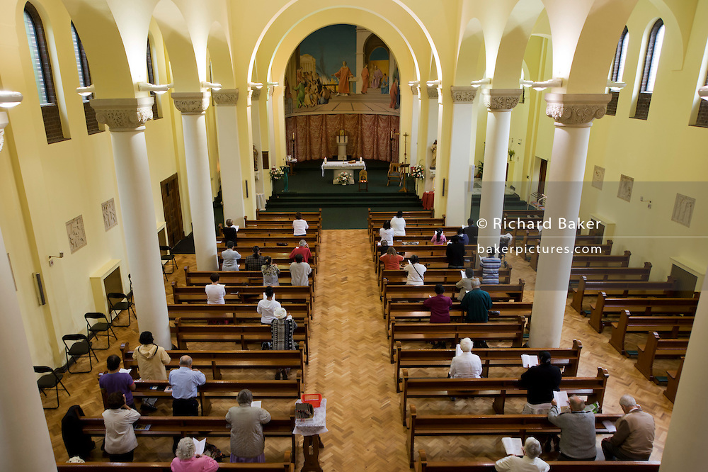 Priest gives blessings during daily Mass at St. Lawrence's Catholic church in Feltham, London.