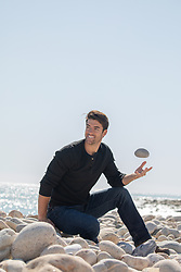 man enjoying time on a rocky beach, tossing a rock in the air