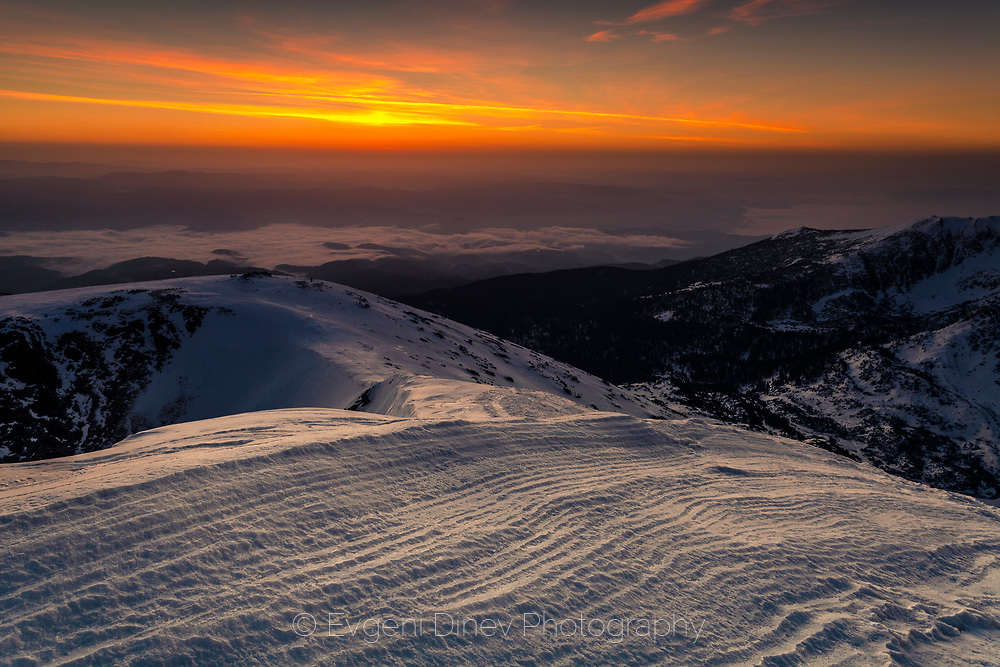 View to the lowland from the mountain peak in winter time at sunrise