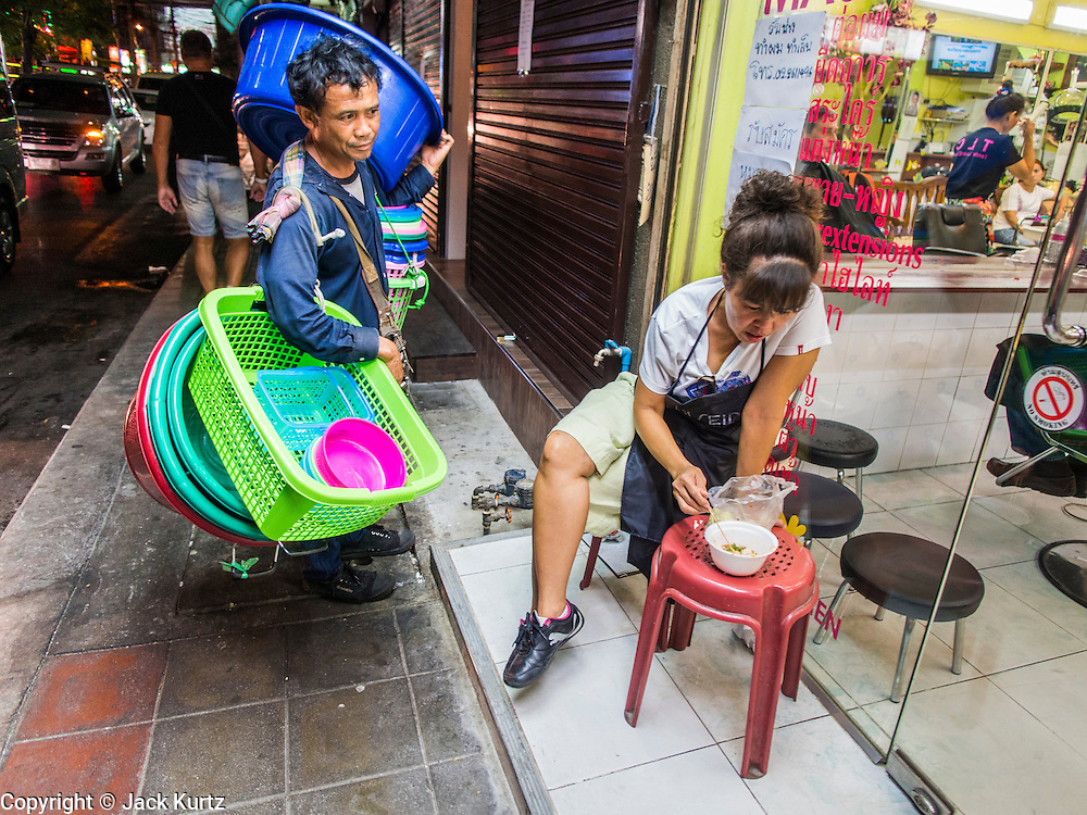"22 MAY 2014 - BANGKOK, THAILAND: A street vendor sells plastic tubs and baskets near the Soi Cowboy ""adult entertainment"" district after the Thai army announcement of a coup replacing the civilian government. The Thai army suspended civilian rule, suspended the constitution and declared the ""military takeover of the nation."" The announcement came just before evening as a meeting between civilian politicians and the army was breaking up with no progress towards resolving the country's political impasse. Civilian politicians were arrested when the meeting ended. The army also declared a curfew from 10PM until 5AM.    PHOTO BY JACK KURTZ"