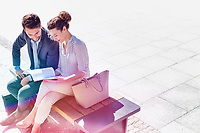 High angle view of businesswoman discussing plans over document with businessman while sitting on bench