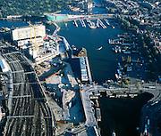 Nederland, Amsterdam, Oosterdok, 17-10-2005; Oosterdokseiland met links (achter de kranen) de hoogbouw van het voormalig expeditiecentrum van de PTT / Hoofdpostkantoor, nu gedeeltelijk Stedelijk Museum (Stedelijk Museum CS); naast de treinsporen (richting Centraal Station) de bouwput van ODE (Oosterdokseiland), project van projectontwikkelaar MAB - Bouwfonds; in en langs het water: drijvend Hotel en Chinees restaurant, de bruggen naar Nemo (wetenschapsmuseum), IJtunnel, Maritiem Museum, binnenvaartschepen, stadsontwikkeling, projectontwikkelaar, city vorming, openbaar vervoer, parkeren, toerisme, economie; <br /> luchtfoto (toeslag), aerial photo (additional fee)<br /> foto /photo Siebe Swart