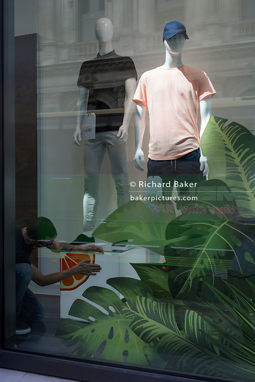 A window designer puts the finishing touches to a display for a clothing retailer in the City of London - the capital's financial district, on 6th June 2018, in London, England.