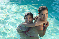 Mother giving daughter piggy back in swimming pool, portrait