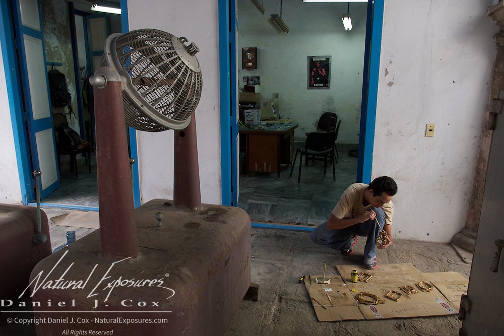 a young man restoring parts of an old building known as the Pawn Shop. Havana, Cuba.