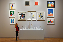 "© Licensed to London News Pictures. 07/02/2017. London, UK. A staff member looks at a collection of works by Kazimir Malevich, including his famous ""Black Square"" and ""Red Square"", at the preview of an exhibition entitled ""Revolution Russian Art 1917-1932"", which marks the centenary of the Russian Revolution.  The exhibition runs from 11 February to 17 April 2017 at the Royal Academy of Arts in Piccadilly. Photo credit : Stephen Chung/LNP"