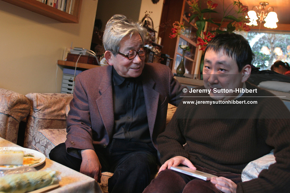 Kenzaburo Oe, Japanese author/essayist/novelist. Born 1935, winner of 1994 Nobel Prize for Literature. Father of Hikari Oe, composer. Photographed at his home in Tokyo, Japan, with son Hikari.