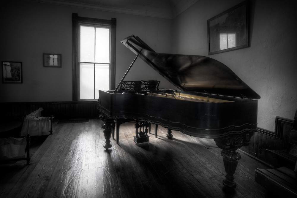A well used piano sits quietly in an old country church in the ozarks.