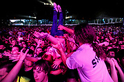 A woman is flipped and lifted over the front row of the mainstage and into the pit in front of the stafe during a Virgin Fest performance at Merriweather Post Pavilion in Columbia, Md.