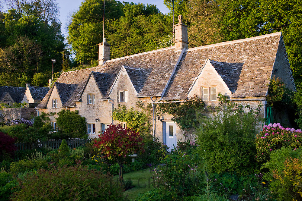 Terrace of traditional Cotswolds stone cottages with front gardens in  Bibury, The Cotswolds, Gloucestershire, UK
