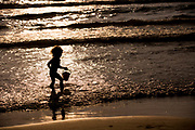 Young boy silhouetted on the beach at sunset carries a bucket in the shallow water