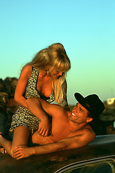playful beautiful woman and her sexy cowboy outdoors