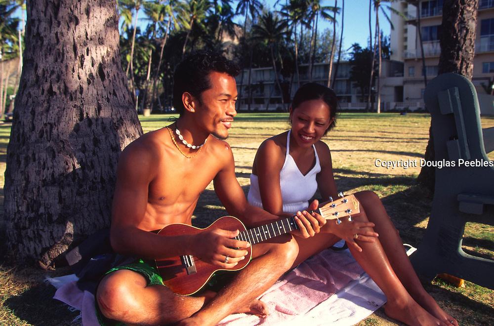 Couple with ukulele, Waikiki, Oahu, Hawaii (editorial use only, no model release)<br />