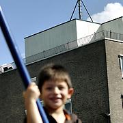 Nederland Rotterdam 27 augustus 2006 20060827.Kind in speelt in woonwijk in speeltuin op schommel met op de achtergrond een umts zendmast  in wijk Charlois Rotterdam Zuid..Foto David Rozing
