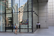 A young mother walks past a businessman standing outside the UBS bank to make a call on Sun Street in the City of London, the capital's financial district - aka the Square Mile, on 8th August, in London, England.