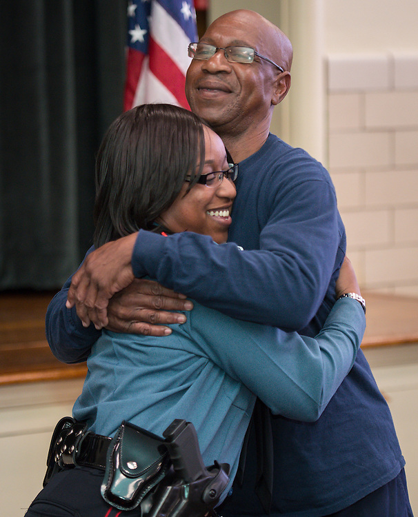 Ashley Williams, left, gets a hug from her father after receiving her badge during a swearing-in ceremony for new officers at the Houston ISD Police Department, March 3, 2014.