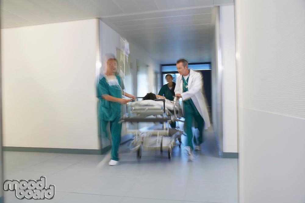 Doctors running Patient on gurney through hospital corridor motion blur