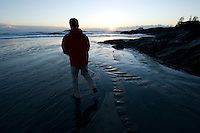 A man walks Chesterman Beach, near Tofino, BC Canada, approximately 3 kilometers of white sand and scattered rock outcroppings, during a winter sunset.
