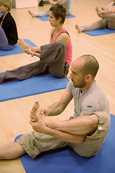 Men and women taking part in a yoga class at Southglade Leisure Centre; Nottingham