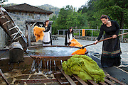 "Evaggelia Drougia (R). Evi (L) and Konstantina (C) Tassiou washing carpets in ""nerotrivi"", the village water whirl for washing clothes and carpets. The water used in nerotrivi flows from the mountains and after entering the whirlpool it ends in Aoos river that goes through the village. No soap is allowed to be used when washing so that the river remains clean. The water flow is enough to clean the carpets and that is why this old way of washing is still used by the local people today."