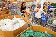 Apr. 3, 2009 -- MESA, AZ: YOSKO HARBER, left, and LAURA QUIGLEY, volunteers at the United Food Bank, fill shopping carts for clients. A spokesperson for the United Food Bank in Mesa, AZ, said demand has increased by more than 100 percent in the last year. She said that at this time in 2008, about 175 people a week (the food bank is open one day a week) bought 200 boxes a food but now they were seeing about 350 people per week and they were buying 400-450 boxes of food per week. Each box of food cost $16 and contains enough food for five meals for two people, including meat, fruit and vegetables and starches. In addition to the food boxes, the food bank gives away perishables, like fresh baked goods and produce, that are donated by Phoenix area grocery stores and food producers. She said the number of donations to the food bank have increased as the economy has worsened but each donation is smaller and the gap between donations and what the food bank needs is widening.    Photo by Jack Kurtz / ZUMA Press