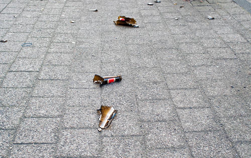 Die Scherben einer zerbrochenen Flasche - Bierflasche - liegen auf einem Gehweg  |