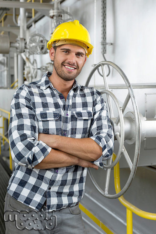 Portrait of young worker with arms crossed leaning on large valve in industry