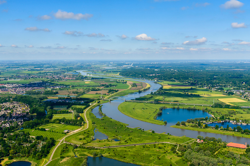 Nederland, Gelderland, Gemeente Arnhem, 29-05-2019; Nederrijn met zicht op de uiterwaarden van Meinerswijk. In de voorgrond het regelwerk (doorlaatwerk met schuiven), onderdeel van de voormalige IJssellinie. Midden plan: Spoorbrug Oosterbeek, dubbelsporige stalen spoorbrug over de Neder-rijn. Spoorwegverbinding tussen Arnhem en Nijmegen. Stuw Driel in het verschiet.<br /> Lower Rhine with view of floodplains and polder Meinerswijk. In the foreground control works (operating with slides), part of the former IJssel defense line. Middle plain:  Railway bridge over river Rhine west of Arnhem<br /> luchtfoto (toeslag op standard tarieven);<br /> aerial photo (additional fee required);<br /> copyright foto/photo Siebe Swart