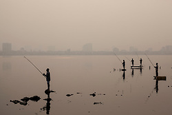 Fishermen on West Lake at dusk in Hanoi, Vietnam, Southeast Asia