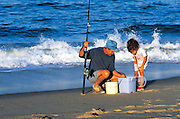 Grandfather and girl fishing on the beach.