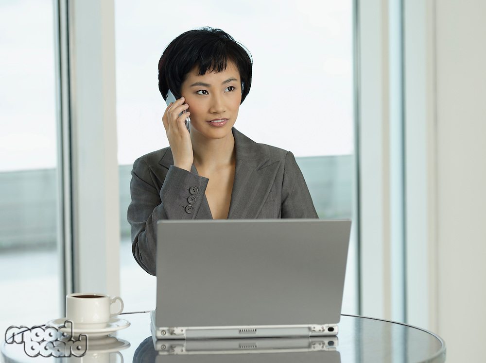 Businesswoman sitting at table with laptop talking on phone
