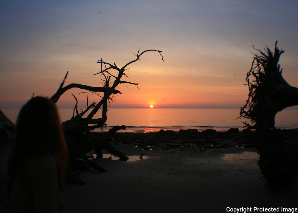 Red head woman at sunrise, sunset on Driftwood Beach, Jekyll Island, fisheye view