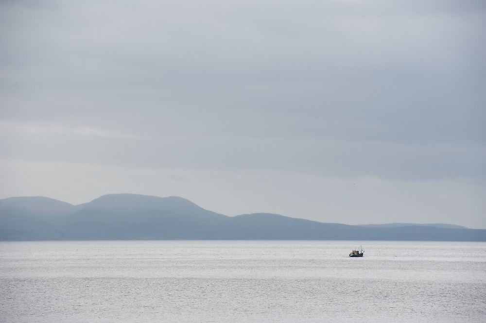 Lonely Fishing Boat on Straights of Magellean with Mountains in Background