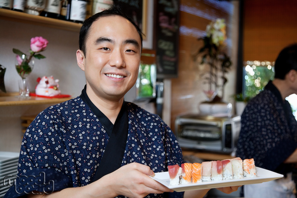 Portrait of a happy chef with sushi in restaurant