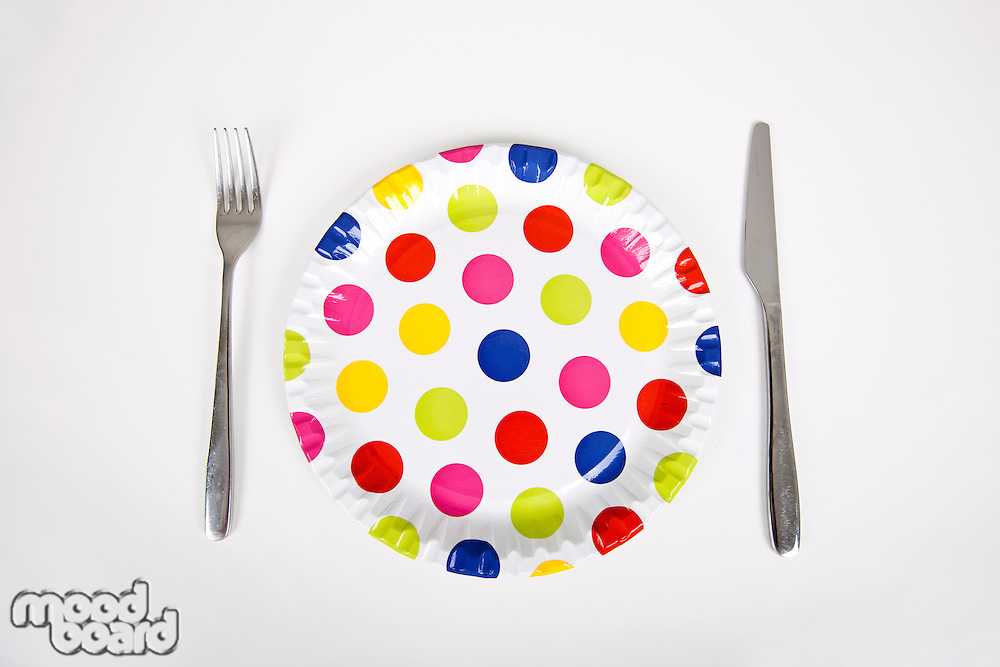 Multicolored plate with polka dots and cutlery against white background