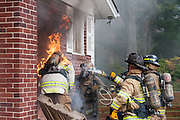 A firefighter sprays water on another fire fighter who is on fire at the entrance of a home.